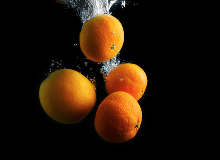오렌지와 공기 방울 물에 산기슭. 과일을 씻어 라. 검정색 배경에 사진입니다. 스톡 콘텐츠