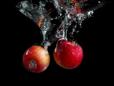 Apples are falling into the water with a splash and air bubbles on a black background. Tasty and healthy food. Wash fruits.
