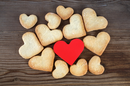 Heart shaped cookies and red heart on wooden background. Top view. photo