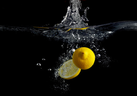 Lemon falling into the water with a splash of water and air bubbles. On a black background. Wash fruits. Stok Fotoğraf