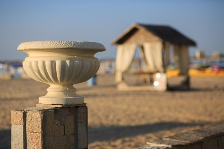 vase plaster: Old plaster vase in antique style on a background of a sandy beach and a canopy. Shallow depth of field. Stock Photo