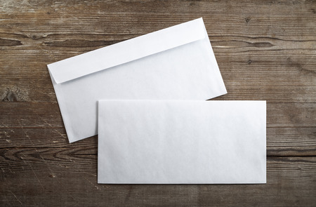 mail envelope: Blank envelopes on a dark wooden background. Back and front. Top view. Template for branding identity.