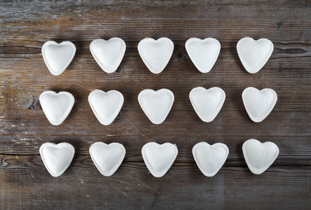 semimanufactures: Dumplings in the form of hearts on a dark wooden background. Top view.
