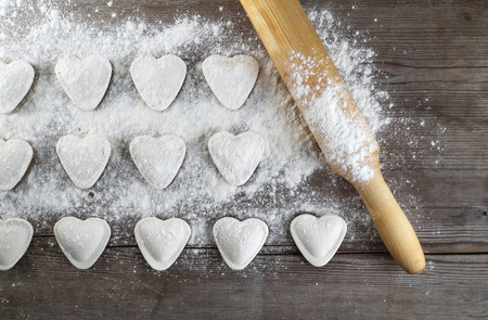 semimanufactures: Cooking dumplings. Raw heart shaped dumplings, flour and rolling pin on wooden background. Top view.