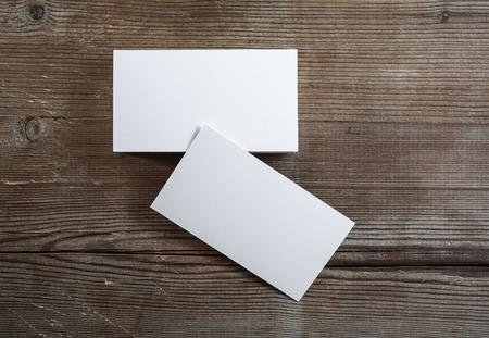 Foto van blanco visitekaartjes op een donkere houten achtergrond. Mock-up voor brandingidentiteit. Bovenaanzicht.