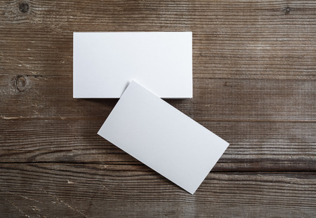 Photo of blank business cards on a dark wooden background. Mock-up for branding identity. Top view.