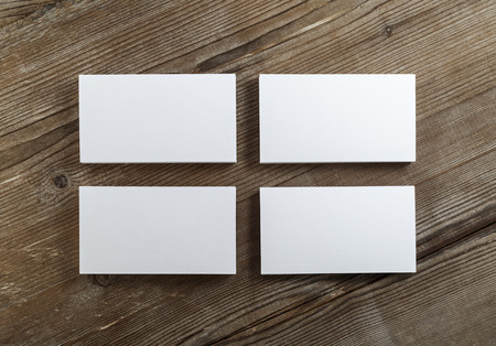 id card: Blank cardboard business cards on a dark wooden table. Template for ID. Top view. on a dark wooden table. Template for ID. Top view. Stock Photo