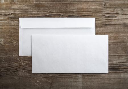 暗い木製の背景の空白の封筒の写真。バックとフロント。アイデンティティをブランディングのテンプレートです。平面図です。