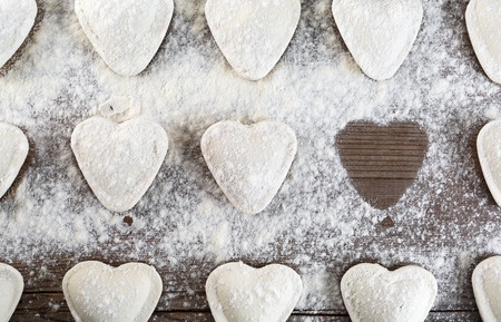 semimanufactures: Cooking dumplings. Raw ravioli in the shape of hearts, sprinkle with flour, on wooden background closeup. Top view.
