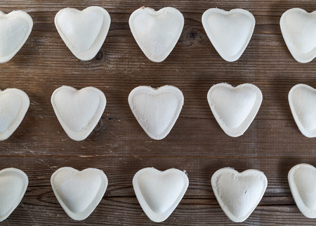 semimanufactures: Raw ravioli in the form of hearts on a dark wooden background closeup. Top view. Stock Photo