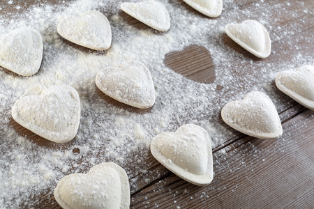 semimanufactures: Cooking ravioli. Raw dumplings in the form of hearts sprinkled flour on wooden background closeup. Shallow depth of field.