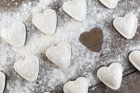semimanufactures: Raw ravioli in the shape of hearts, sprinkle with flour, on dark wooden table. Cooking dumplings. Top view.