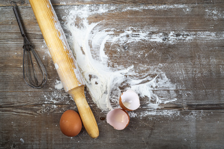 retro kitchen: Eggs, eggshells, flour and rolling pin on wooden background. Top view.