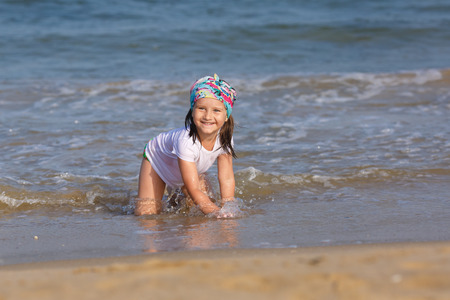 wet t shirt: Happy smiling child playing on the beach at the water