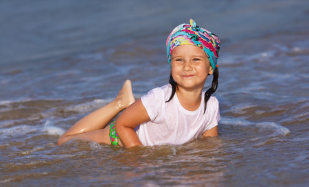Happy little girl in a white t-shirt and colorful bandana having fun in the water at the beach. Stock Photo