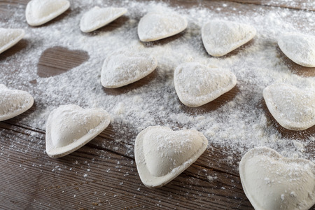 semimanufactures: Raw ravioli in the shape of hearts, sprinkle with flour, on dark wooden background. Cooking dumplings. Shallow depth of field.