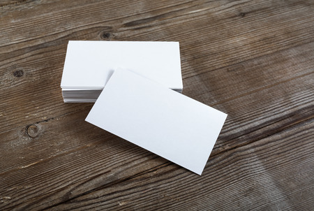 note card: Photo of blank business cards on a wooden background. Template for ID. Top view.