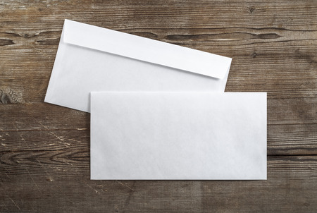 Photo of blank envelopes on a dark wooden background. Back and front view. Template for ID. Top view.