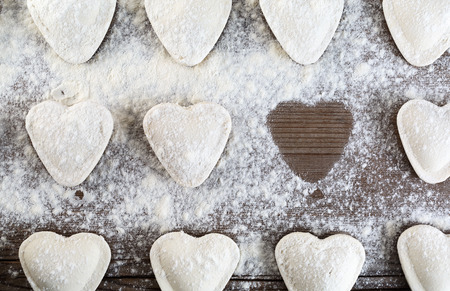 semimanufactures: Raw ravioli in the shape of hearts, sprinkle with flour, on wooden background closeup. Cooking dumplings. Top view. Stock Photo