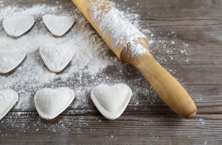 semimanufactures: Raw heart shaped dumplings, flour and rolling pin on wooden background. Cooking ravioli. Shallow depth of field.