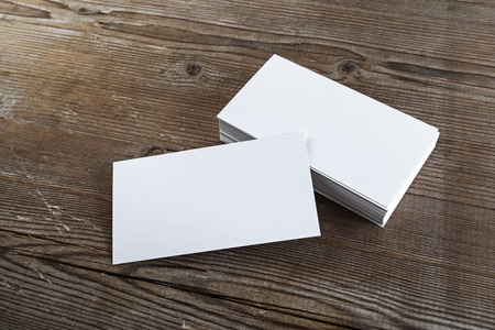 Blank white business cards on a dark wooden background. Mockup for branding identity. Shallow depth of field.