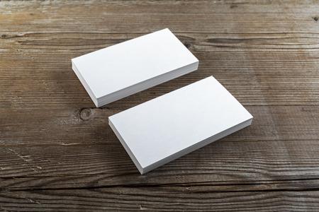 暗い木製の背景の空白の名刺の 2 つのスタック。アイデンティティをブランディングのテンプレートです。フィールドの浅い深さ。