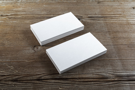 Two stacks of blank business cards on a dark wooden background. Template for branding identity. Shallow depth of field.