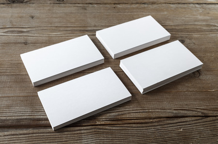 Four stacks of blank business cards on a dark wooden background. Mockup for branding identity. Shallow depth of field.