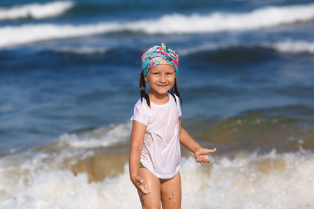 wet t shirt: Happy child in a white t-shirt and colorful headdress against a blurred background of ocean waves on a sunny day. Shallow depth of field. Focus on the model
