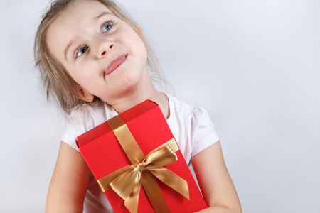 Little girl holding a red gift box with golden ribbon tied bow. Child stuck out his tongue with pleasure. Space for text. photo