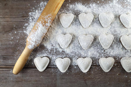 semimanufactures: Heart shaped dumplings, flour and rolling pin on wooden background. Cooking ravioli. Top view. Stock Photo
