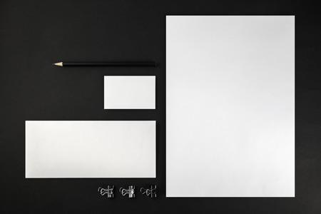 hoja en blanco: Artículos de papelería en blanco y Modelo de la identidad corporativa en el fondo oscuro. Para las presentaciones de diseño y carteras. Vista superior.
