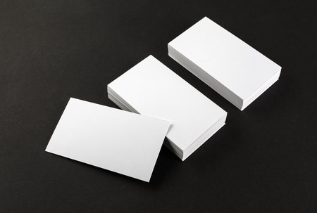 business cards design: Photo of blank business cards on a black background. Template for branding identity. Top view. Shallow depth of field.