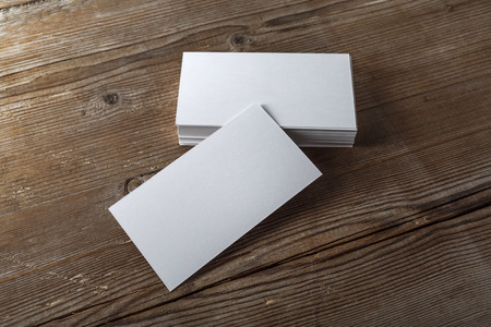 mockup: Blank white business cards on a dark wooden background. Mockup for branding identity. Template for graphic designers portfolios. Top view. Shallow depth of field.