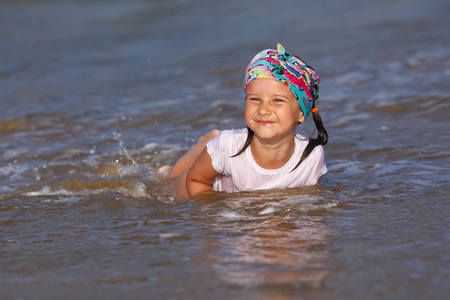 wet t shirt: Happy little girl in a white t-shirt and colorful bandana having fun in the water at the beach. Shallow depth of field. Focus on the model