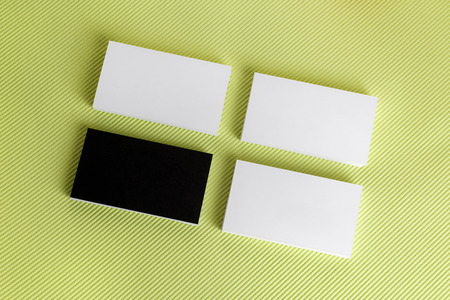 Foto van blanco visitekaartjes op groene achtergrond. Sjabloon voor ID. Bovenaanzicht.