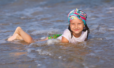 wet t shirt: Happy child in a white t-shirt and colorful bandana having fun in the water at the beach. Shallow depth of field. Focus on the model