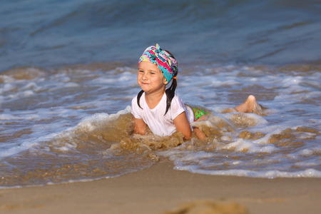 Happy little child in a white t-shirt and colorful bandana having fun in the water at the beach. Shallow depth of field. Focus on the model. Stock Photo