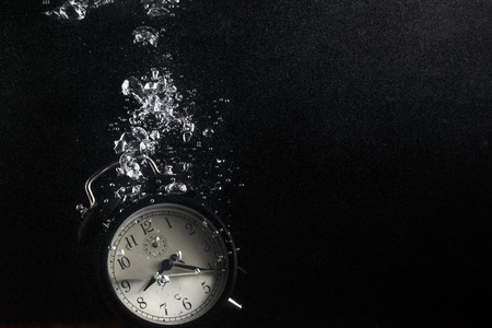 end of time: Concept of time. Vintage alarm clock in water with air bubbles. Photo on black . Plenty of space for text.