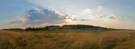 Sunset in the countryside. Panoramic rural landscape with a beautiful sky and sunshine. photo