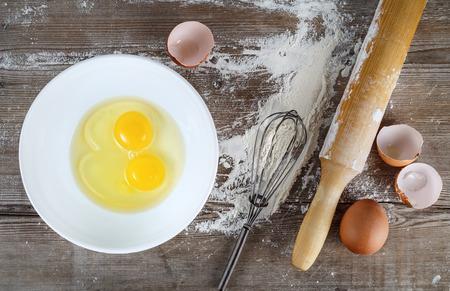 huevo blanco: Cocina de fondo con los huevos, los huevos crudos en un plato, c�scaras de huevo, harina, palo de amasar y batir en un fondo de madera. Vista superior.
