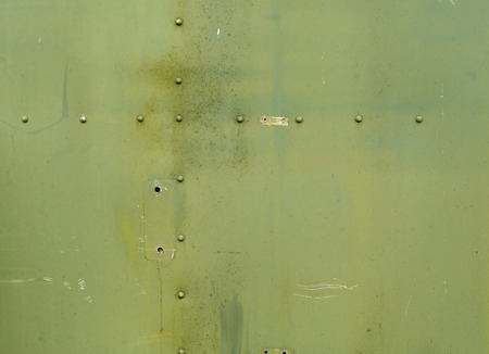 Abstract painted matte green metal background texture with rivets. Riveted  military green metal. Stok Fotoğraf - 39494763