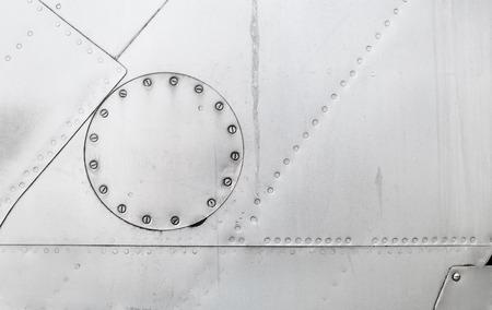 Abstract verweerde zilver metallic achtergrond. Metalen structuur met klinknagels en bouten. Mantel oud vliegtuig. Stockfoto