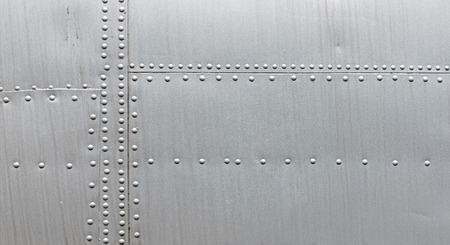 Silver metal texture with rivets. Abstract weathered metallic background.