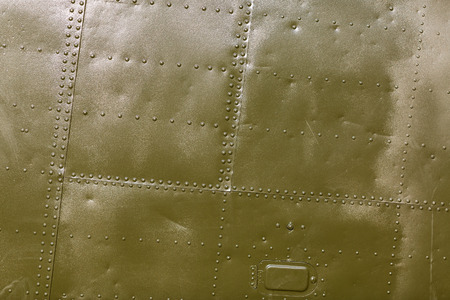 Military green metal plates background texture with seams and rivets. Riveted metal from aircraft.