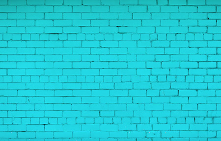 Brick wall painted in bright turquoise color. The texture of the brickwork.