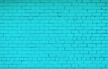 Bakstenen muur geschilderd in heldere turquoise kleur. De textuur van het metselwerk. Stockfoto