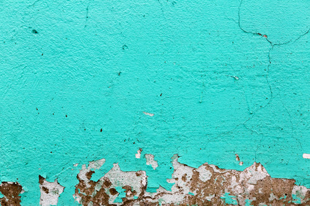 Turquoise texture. Peeling paint background.  A fragment of the old wall, painted bright turquoise paint, cracked over time.