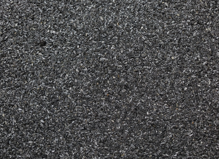 ruberoid: Abstract dark granular background. Abrasive texture roofing material close-up.