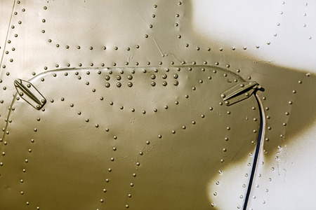 Abstract painted khaki metal background with rivets.  Fragment of old military aircraft. photo